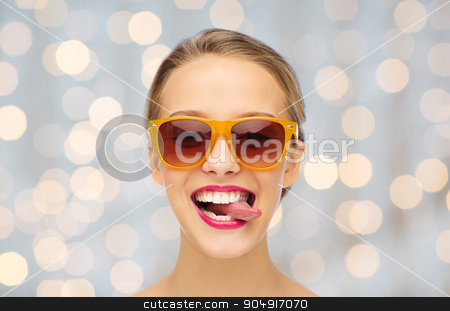 happy young woman in sunglasses showing tongue stock photo, people, expression, joy and fashion concept - smiling young woman in sunglasses with pink lipstick on lips showing tongue over holidays lights background by Syda Productions