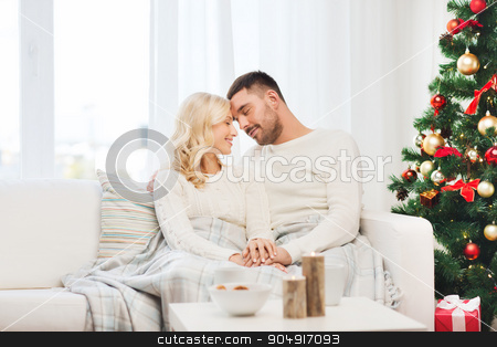 happy couple at home with christmas tree stock photo, family, christmas, holidays, love and people concept - happy couple covered with plaid sitting on sofa at home by Syda Productions