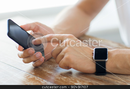 close up of hands with smart phone and watch stock photo, business, technology and people concept - close up of male hand holding smart phone and wearing watch at home by Syda Productions
