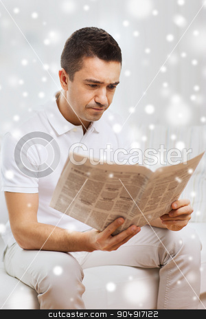 sad man reading newspaper at home stock photo, leisure, information, people and mass media concept - sad man reading newspaper at home with snow effect by Syda Productions