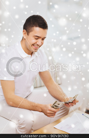 man with papers counting money at home stock photo, business, savings, finances, income and people concept - man with papers counting money at home over snow effect by Syda Productions