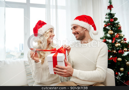 happy couple at home with christmas gift box stock photo, christmas, holidays and people concept - happy couple in santa hats with gift box sitting on sofa at home by Syda Productions