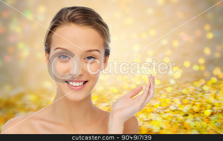 smiling young woman face and shoulders stock photo, beauty, people and health concept - smiling young woman face and shoulders over golden glitter or holidays lights background by Syda Productions