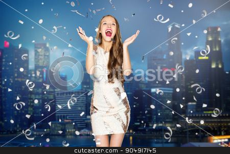 happy young woman or teen girl over night city stock photo, people, holidays, emotion and glamour concept - happy young woman or teen girl in fancy dress with sequins and confetti at party over night singapore city background by Syda Productions