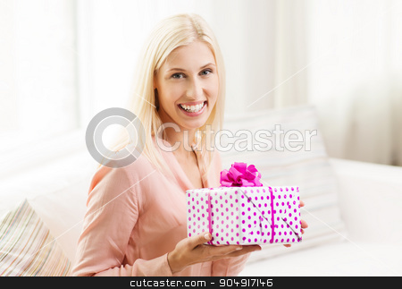 smiling woman with gift box at home stock photo, people, holidays, celebration and birthday concept - smiling young woman with gift box at home by Syda Productions