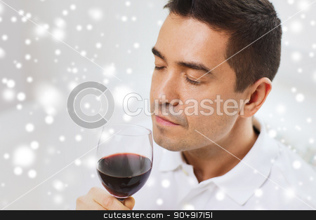 happy man drinking red wine from glass at home stock photo, profession, drinks, leisure and people concept - happy man drinking and smelling red wine from glass over snow effect by Syda Productions