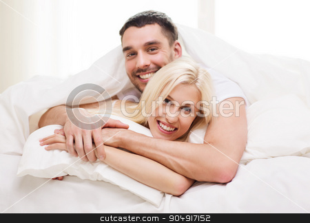 happy couple lying in bed and hugging at home stock photo, people, family, bedtime and happiness concept - happy couple lying in bed and hugging at home by Syda Productions