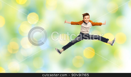 happy smiling boy jumping in air stock photo, happiness, childhood, freedom, movement and people concept - happy smiling boy jumping in air over green summer holidays lights background by Syda Productions