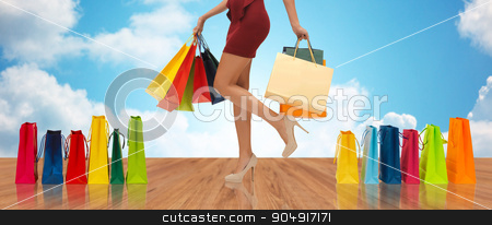 close up of woman on high heels with shopping bags stock photo, people, sale and consumerism concept - close up of woman in red short skirt and high heeled shoes with shopping bags by Syda Productions