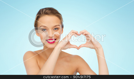 smiling young woman showing heart shape hand sign stock photo, beauty, people, love, valentines day and make up concept - smiling young woman with pink lipstick on lips showing heart shape hand sign over blue background by Syda Productions
