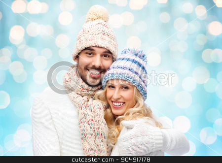 happy couple in winter clothes hugging over lights stock photo, winter, fashion, couple, christmas and people concept - smiling man and woman in hats and scarf hugging over blue holidays lights background by Syda Productions
