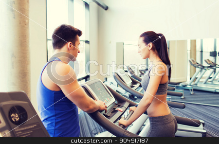 woman with trainer on treadmill in gym stock photo, sport, fitness, lifestyle, technology and people concept - woman with trainer working out on treadmill in gym by Syda Productions