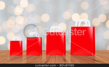 many blank red shopping bags stock photo, sale, consumerism, advertisement and retail concept - many blank red different size shopping bags by Syda Productions