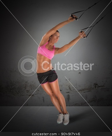 Training with the TRX stock photo, Woman fitness instructor training with the TRX by Federico Caputo