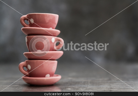 Little Pink Toy Porcelain Cups and Plates with White Dots stock photo, Little pink toy porcelain cups and plates with white dots on gray background by OZMedia