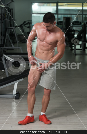 Muscular Man Flexing Muscles In Gym stock photo, Awesome Bodybuilder Showing His Muscles And Posing In Gym by Jasminko Ibrakovic