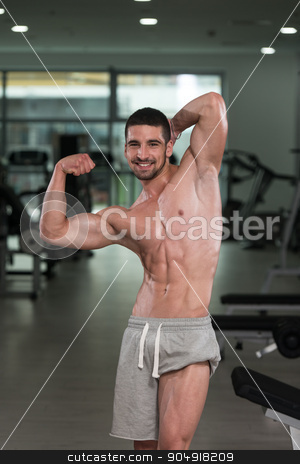 Bodybuilder Performing Rear Biceps Pose stock photo, Awesome Bodybuilder Showing His Muscles And Posing In Gym by Jasminko Ibrakovic