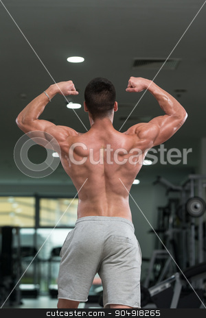 Detail Of A Bodybuilder Posing In The Gym stock photo, Awesome Bodybuilder Showing His Muscles And Posing In Gym by Jasminko Ibrakovic