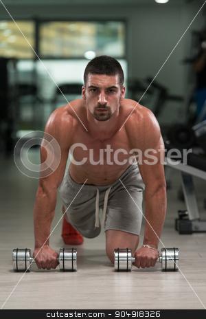 Pushups With Dumbbels stock photo, Young Athlete Doing Pushups With Dumbbells As Part Of Bodybuilding Training by Jasminko Ibrakovic
