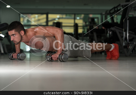 Push Ups With Dumbbels stock photo, Young Athlete Doing Pushups With Dumbbells As Part Of Bodybuilding Training by Jasminko Ibrakovic
