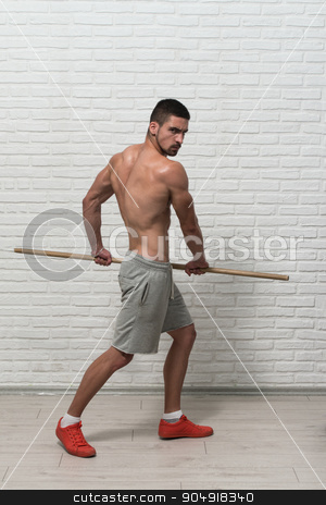Bodybuilder Is Exercising With Stick At The Wall stock photo, Athlete Muscular Bodybuilder Emotional Posing At The Wall With Stick by Jasminko Ibrakovic