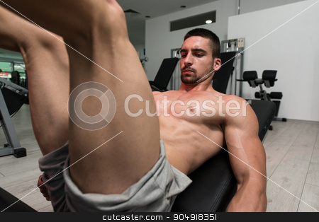 Man In Gym On Machine Exercising stock photo, Young Man Using The Leg Press Machine At A Health Club In Gym by Jasminko Ibrakovic