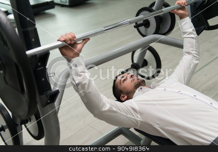 Businessman Exercise Bench Press With Barbell stock photo, Business Man In Gym Exercising Chest On The Bench Press by Jasminko Ibrakovic