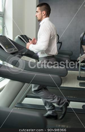 Businessman Running On Treadmill In Gym stock photo, Businessman Running On Treadmill At A Health Club by Jasminko Ibrakovic