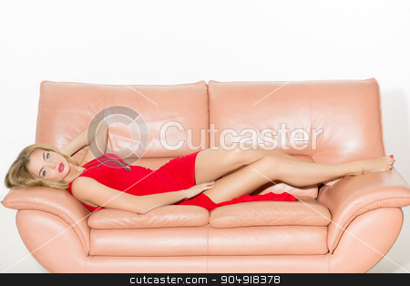 full-length portrait of beautiful young blond woman on couch. long curly hair. Red dress stock photo, full-length portrait of beautiful young blond woman on couch by Kopytin Georgy