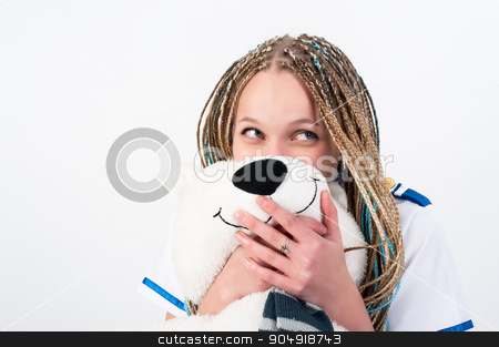 Beautiful young woman with funny face stock photo, A portrait picture on lovely young attractive woman with long braid hair in stewardess uniform hiding behind white bear over white background by Aikon