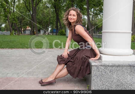 portrait of young beautiful woman in city park stock photo, Young attractive brunette woman wearing brown dress at summer park by Aikon