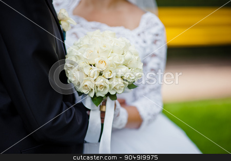 Wedding bouquet of white rose in hands of newlywed stock photo, Wedding bouquet of white rose in hands of newlywed by Andrii Shevchuk