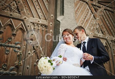 Wedding couple near old wooden door of catholic church stock photo, Wedding couple near old wooden door of catholic church by Andrii Shevchuk