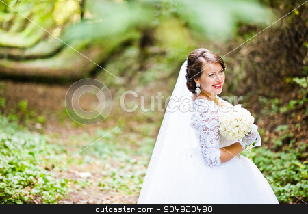 Happy smiled bride at green alley stock photo, Happy smiled bride at green alley by Andrii Shevchuk