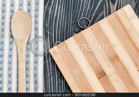 Wooden Spoon on Napkin, Chopping Board and Blue Wooden Backgroun stock photo, Wooden spoon on napkin, chopping board on blue wooden background by OZMedia