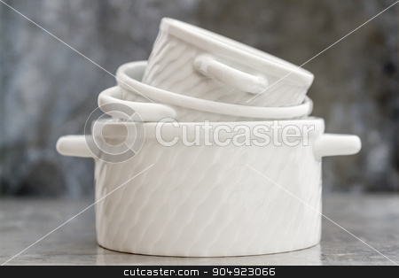 Empty White Porcelain Saucepans Without Covers stock photo, Empty white porcelain saucepans without covers on gray background by OZMedia