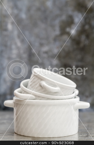 Empty White Porcelain Saucepans Without Covers stock photo, Empty white porcelain saucepans without covers on gray background with copy space by OZMedia