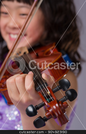 Young Japanese Girl Portrait with Violin stock photo, A portrait of a cute, happy and young Japanese girl in a purple dress with a violin with the focus on her hand instead of her face. by Scott Dumas