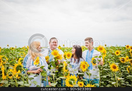 Happy family having fun on sunflowers stock photo, Happy family having fun on sunflowers by Andrii Shevchuk