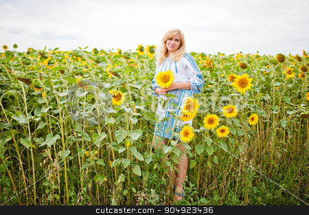 Adult blonde woman at field of sunflowers stock photo, Adult blonde woman at field of sunflowers by Andrii Shevchuk