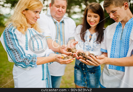 Happy family on pine forest holding cones at hand stock photo, Happy family on pine forest holding cones at hand by Andrii Shevchuk