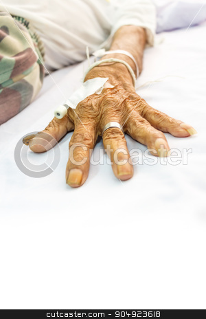 old patient's hand with plug on bed in hospital stock photo, old patient's hand with plug on bed in hospital and blank area at lower side for fill text by stockdevil