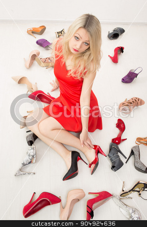 girl in red dress sitting on the floor. Selects shoes. Trying on shoes. beautiful sexy blonde stock photo, girl in red dress sitting on the floor. Selects shoes. Trying on shoes by Kopytin Georgy