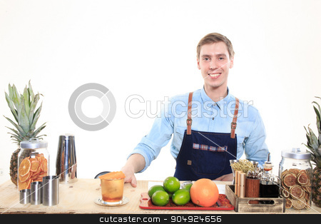 bartender with a shaker and bottle on white background. behind the bar stock photo, Young bartender with a shaker and bottle on white background by Kopytin Georgy