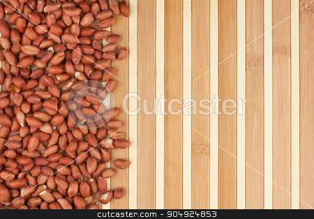 Peeled peanuts lies on a wooden mat stock photo, Peeled peanuts lies on a wooden mat by alekleks