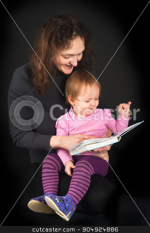 Pretty mother with daughter reading book with tales stock photo, Attractive mother shows pictures in book to her cute little 15 monthes old daughter over black background by Aikon