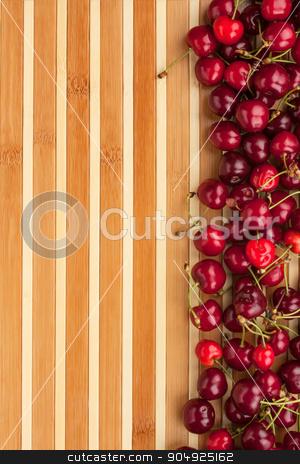 Cherry lying on bamboo mat stock photo, Cherry lying on bamboo mat, can be used as background by alekleks