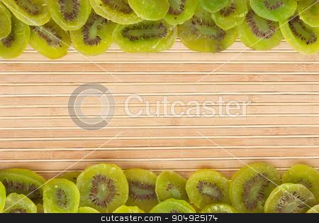 Dried kiwi lying on a bamboo mat stock photo, Dried kiwi lying on a bamboo mat, as background by alekleks