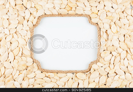 Figured frame made of rope with  pumpkin seeds  lying on a white stock photo, Figured frame made of rope with  pumpkin seeds  lying on a white background, with place for your text, graphics by alekleks