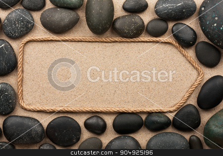 Pointer made of rope with black stones stock photo, Pointer made of rope with black stones, lying on the sand by alekleks